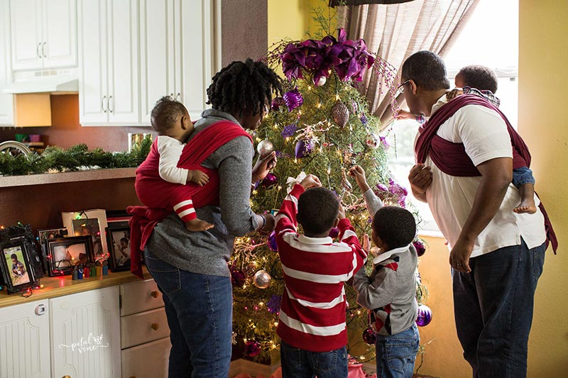Decorating a Christmas Tree with small kids and wrapped baby