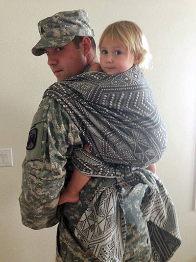 Military Dad babywearing toddler in a Rucksack TUB (tied under bottoM) with a size 3 woven wrap.